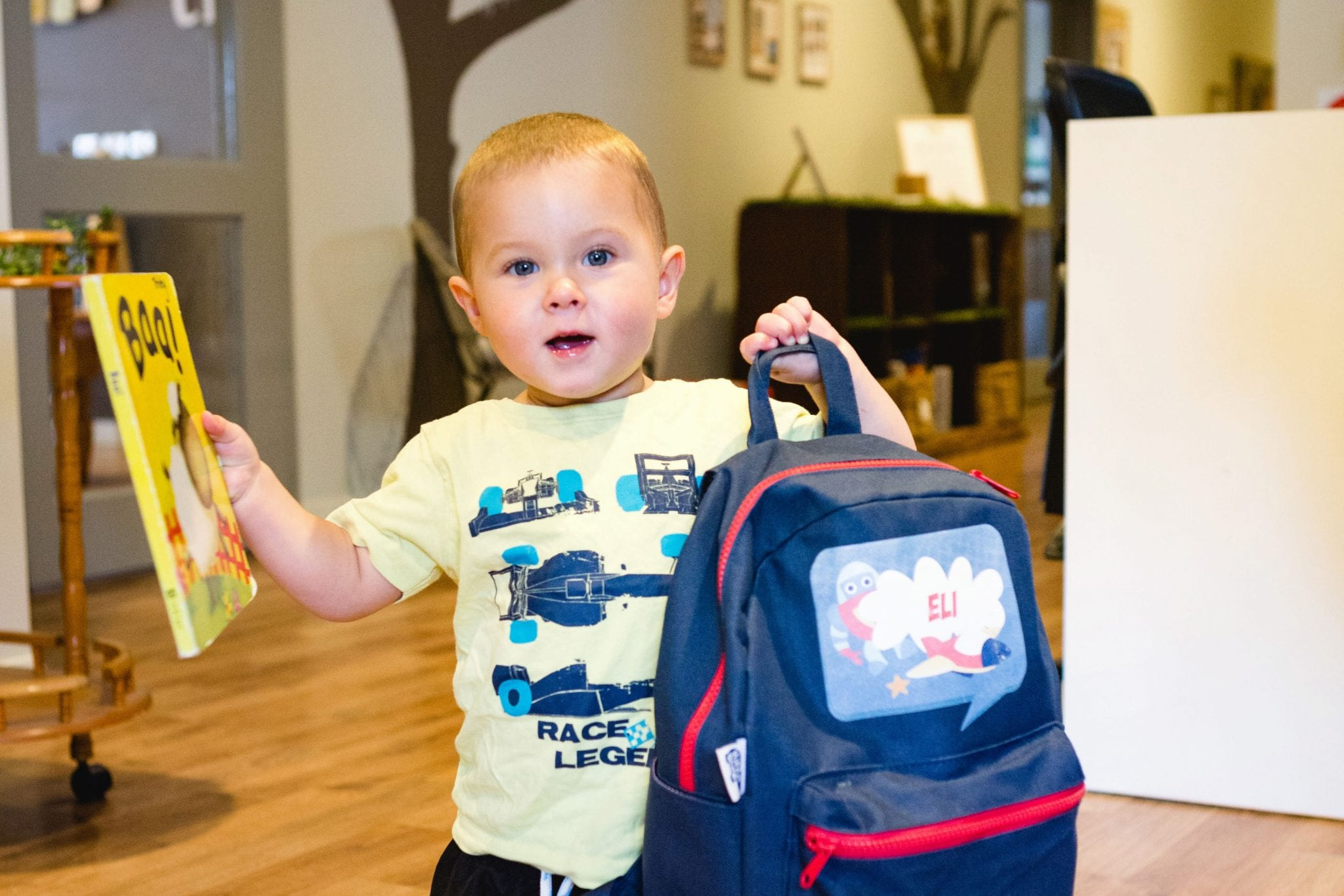 Toddler-holding-bag-at-drop-off-in-childcare-centre-foyer