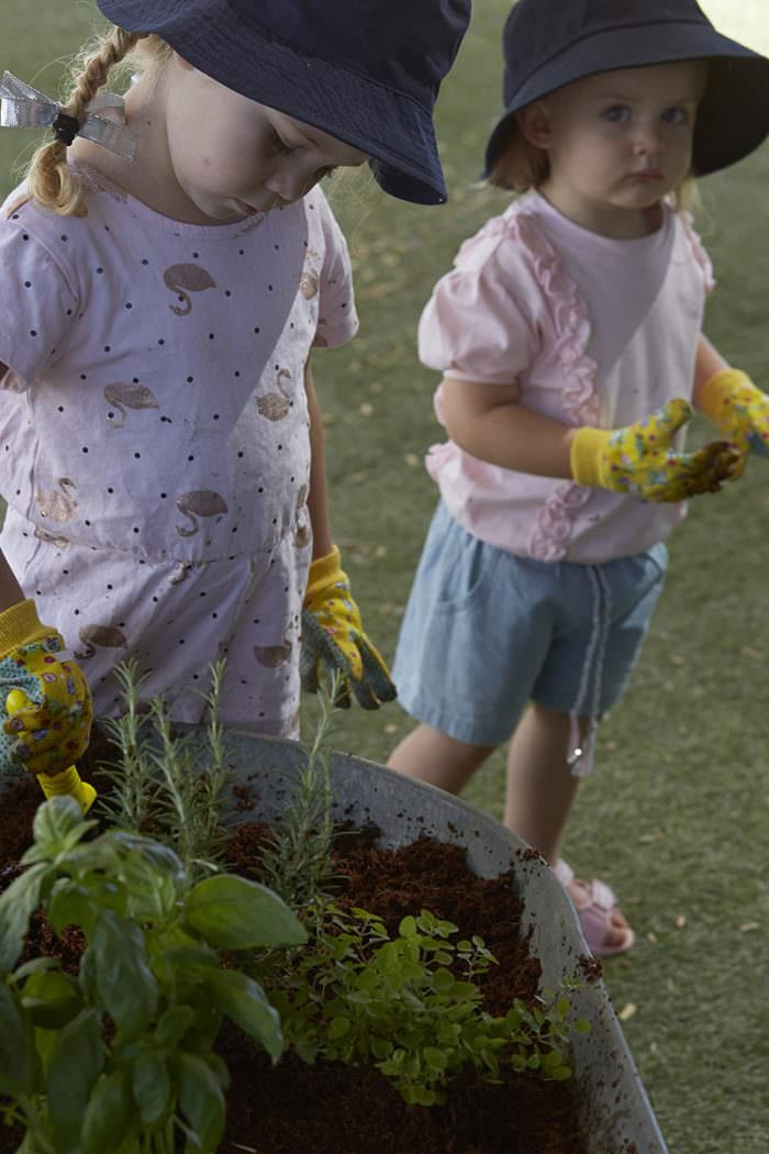 two girls planting herbs in wheelbarrow with childrens gloves and spades