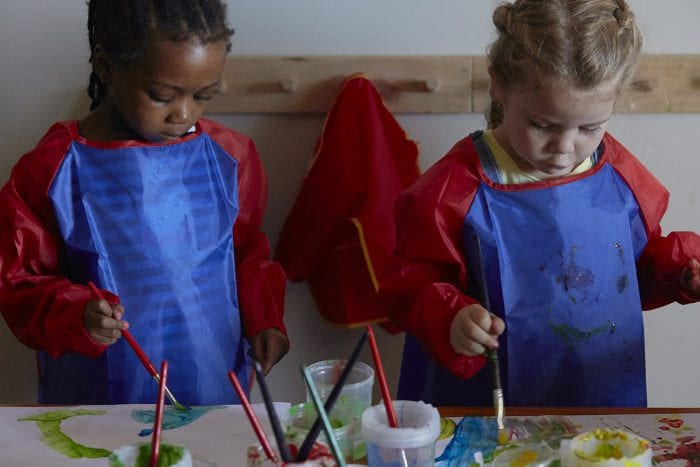 two little girls painting with paintbrush and colorful paints