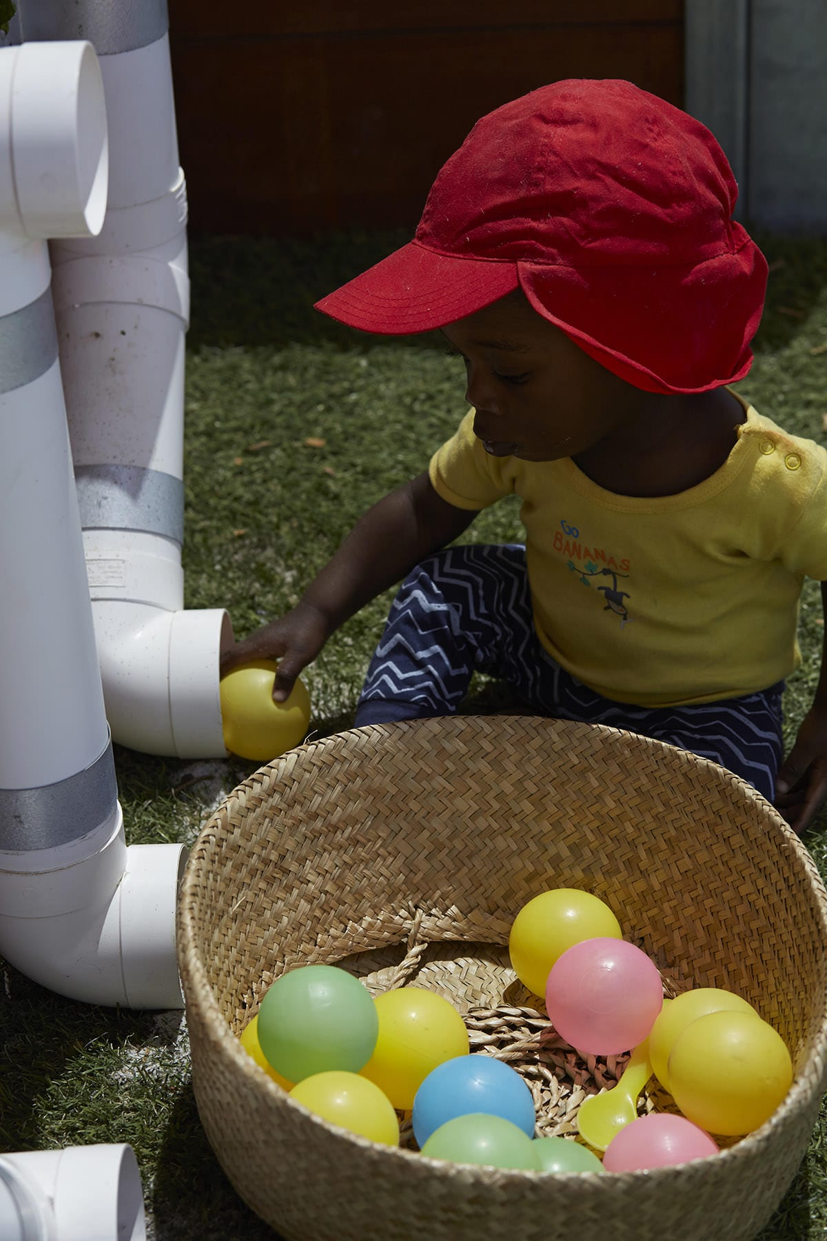 Baby boy playing outside with balls and recycled pipes at early learning centre