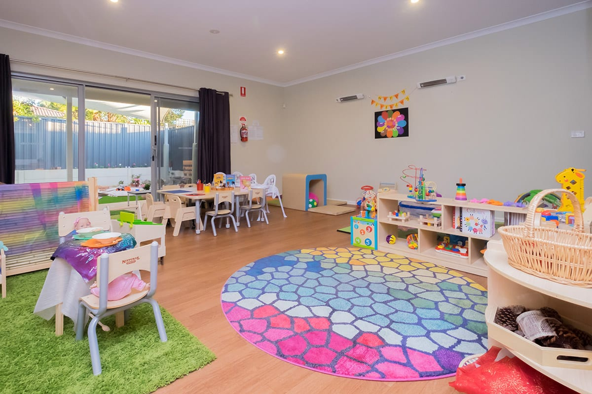 Toddler room with colourful mat and toys set up on shelves at Keiki early learning hamersley