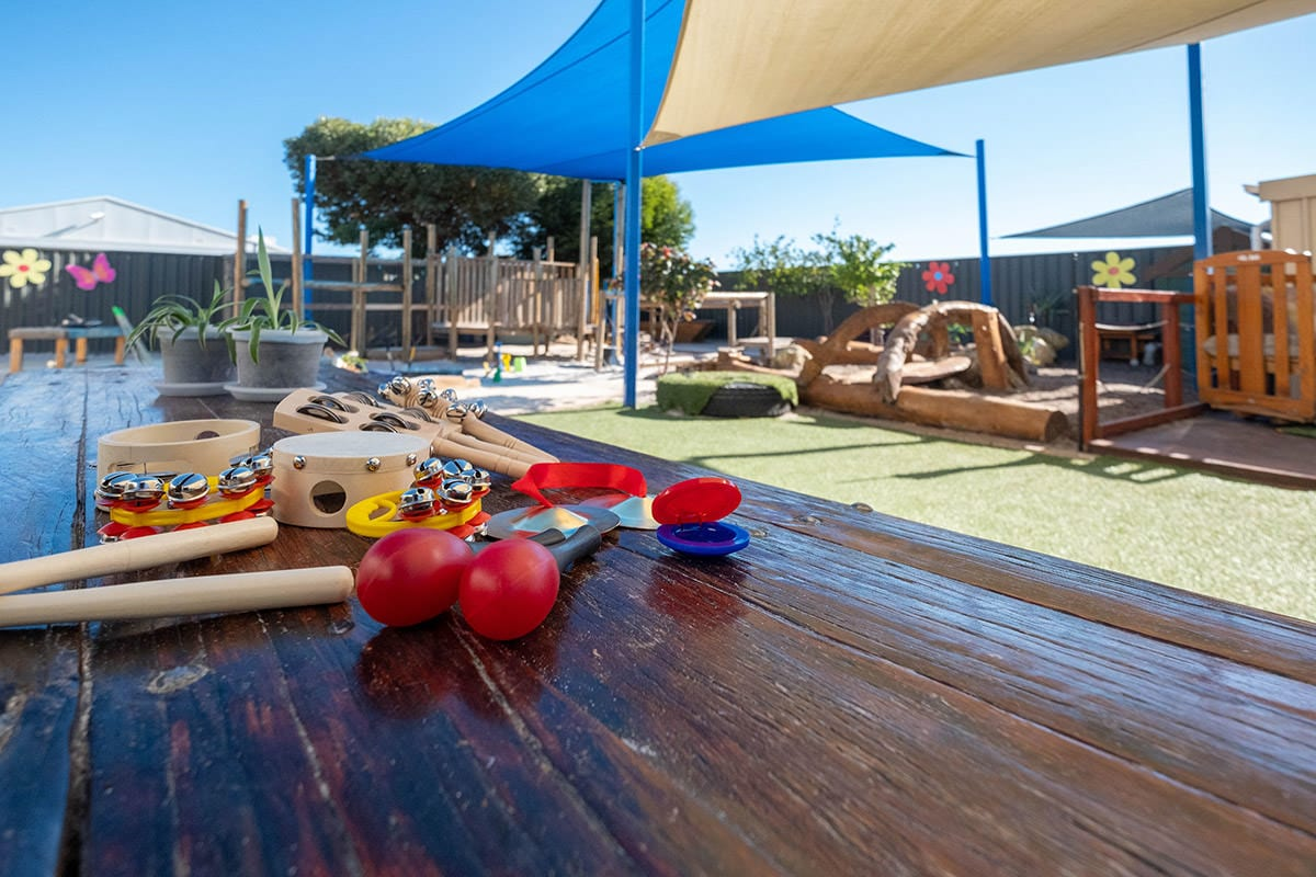Kindy outdoor environment with musical instruments on wooden table and wooden play structures at keiki early learning mindarie keys