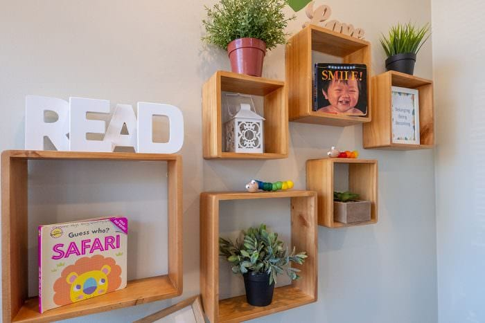 Square bookshelves on community library wall with READ letters, books and plants