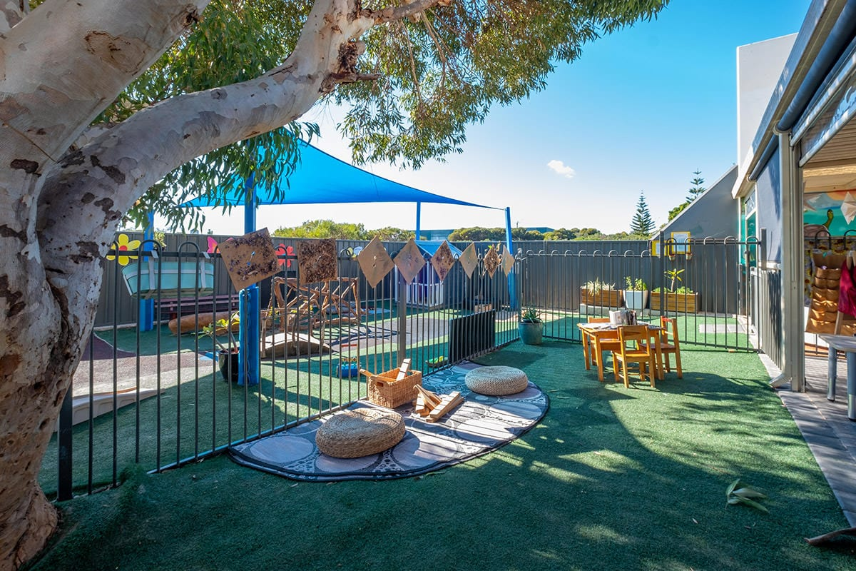Outdoor toddler environment with wooden block area and child sized table and chairs at keiki early learning mindarie keys