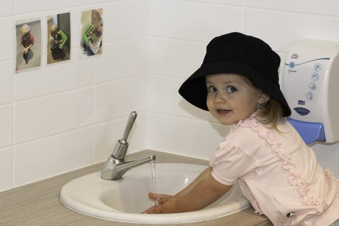 Toddler girl washing hands in childcare sink