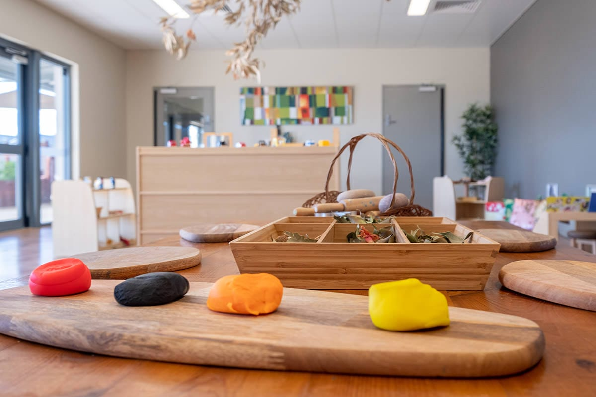 red, black, orange and yellow play dough in natural childcare centre