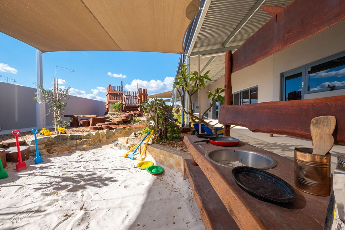 Kindy and toddler shared outdoor environment wooden sandpit kitchen with colourful shovels and large wooden structure at keiki early learning trinity alkimos