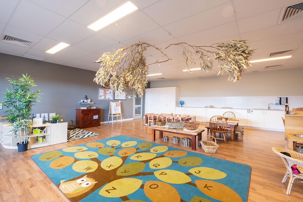 Kindy indoor environment large alphabet mat wooden tables and chairs tree branches hanging from ceiling at keiki early learning trinity alkimos