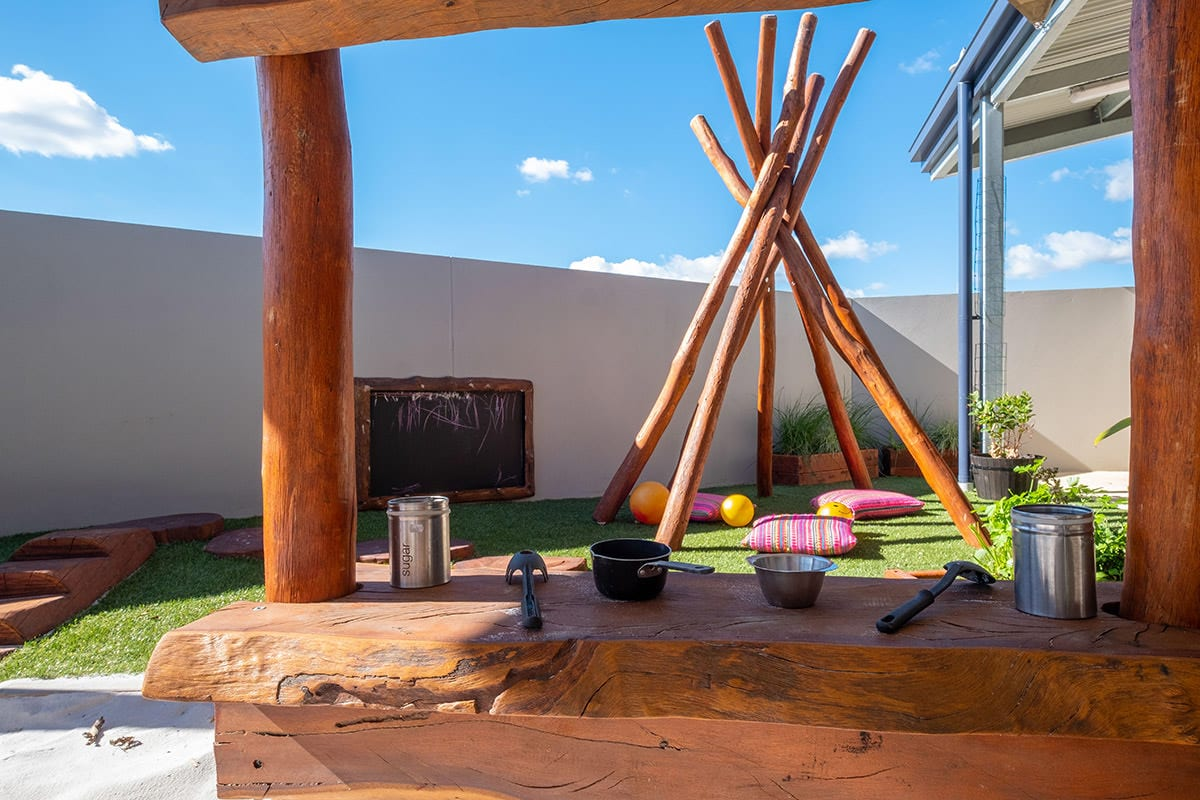 Baby outdoor environment with wooden structure in sandpit with cooking utensils chalk board on back wall and large woodnen posts to make a tepee with grass pillows and balls underneath at keiki early learning trinity alkimos