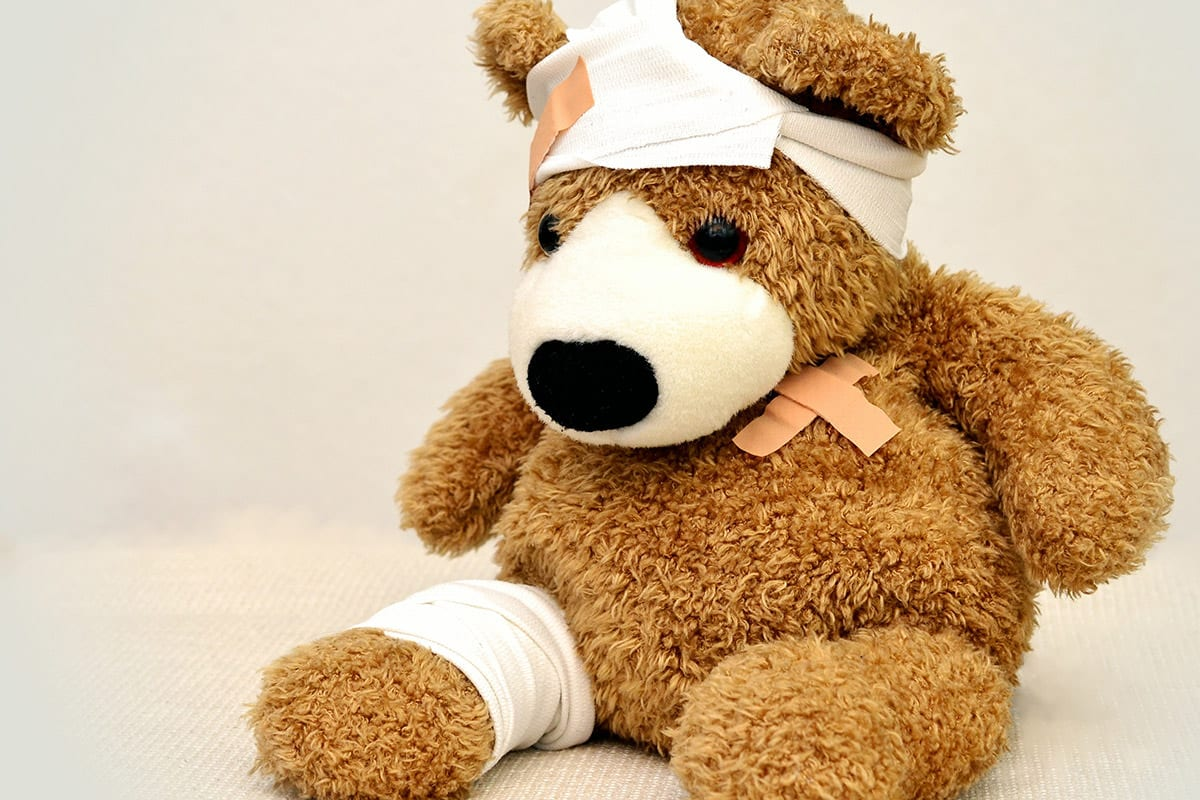 teddybear with band aids and bandages on head chest and leg
