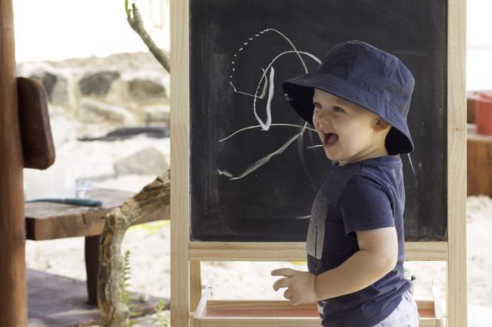 happy kid enjoying drawing on blackboard