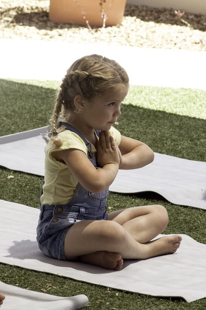 kindy aged girl doing yoga meditation pose at early learning school