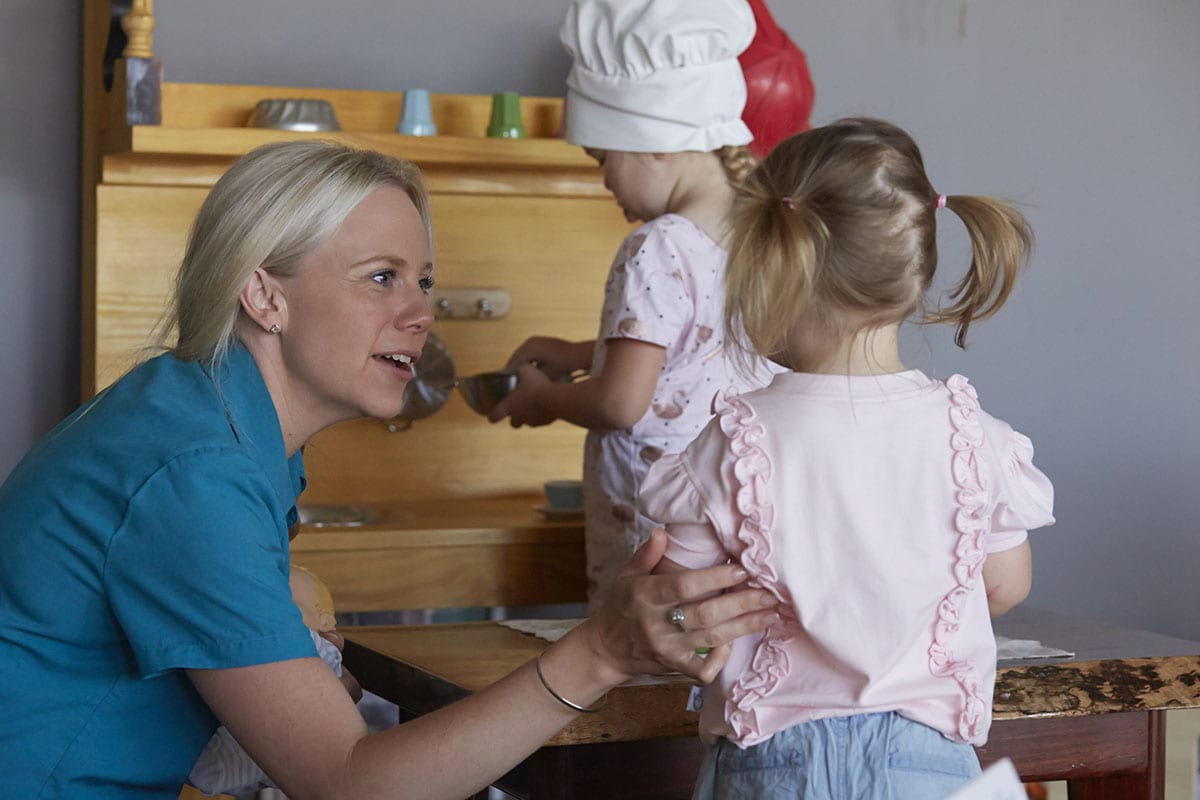 educator reassuring little girl playing in childcare centre