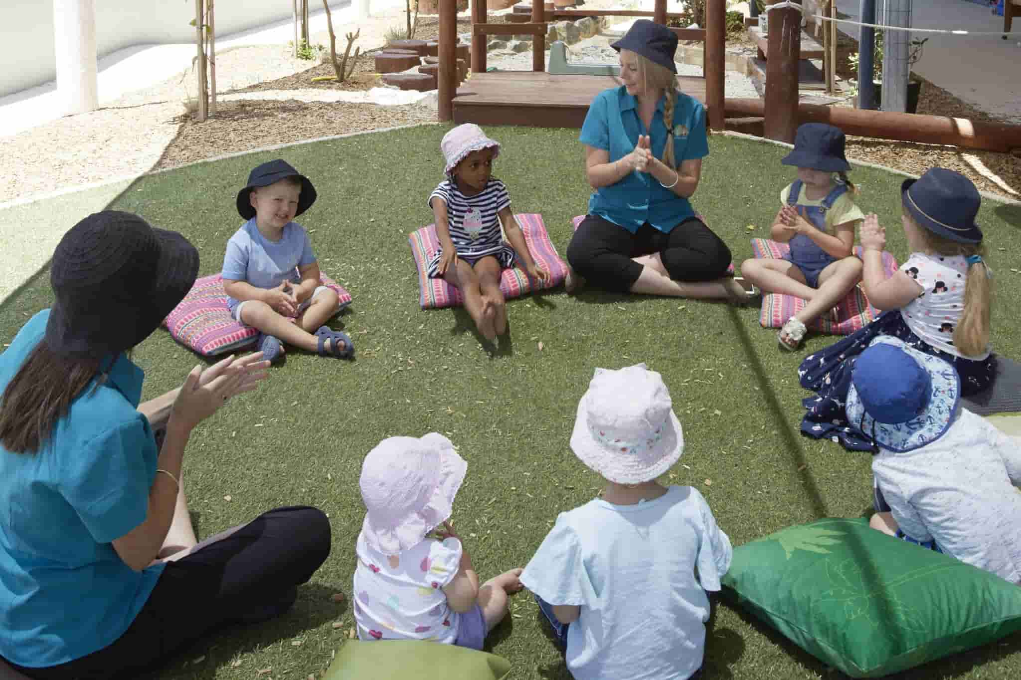 children singing in a circle with educators at Early Learning centre outdoor area