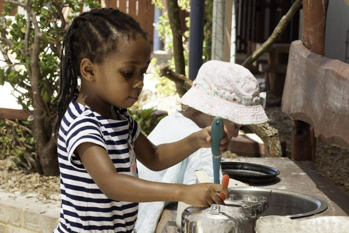 two kindy children playing in in outdoor kitchen