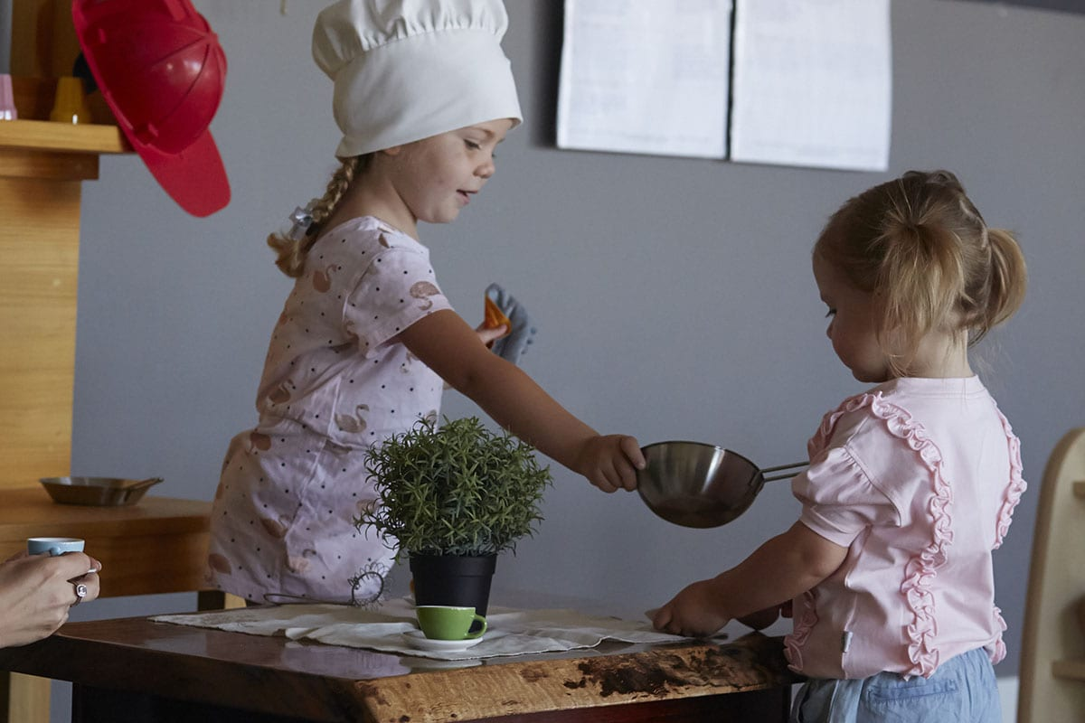 two young girls playing with kitchen props together at wooden table