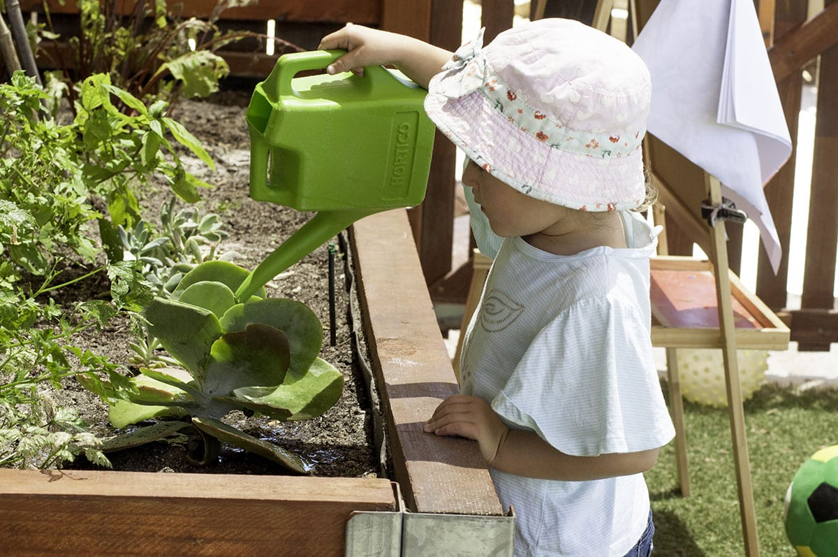 young girl watering plants with watering can at childcare