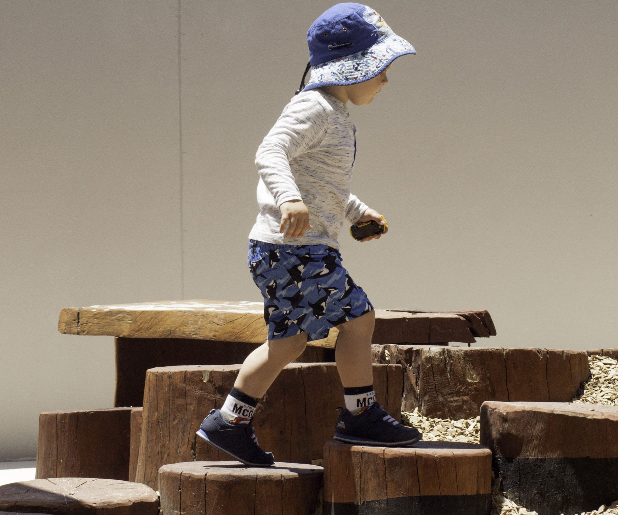 young boy climbing wooden steps outdoors