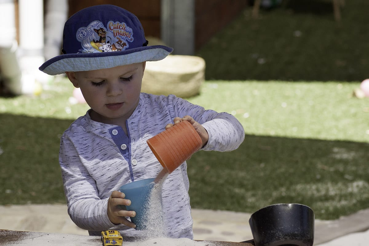 Young-boy-outside-pouring-sand-from-one-cup-into-another-Keiki-early-learning-Trinity