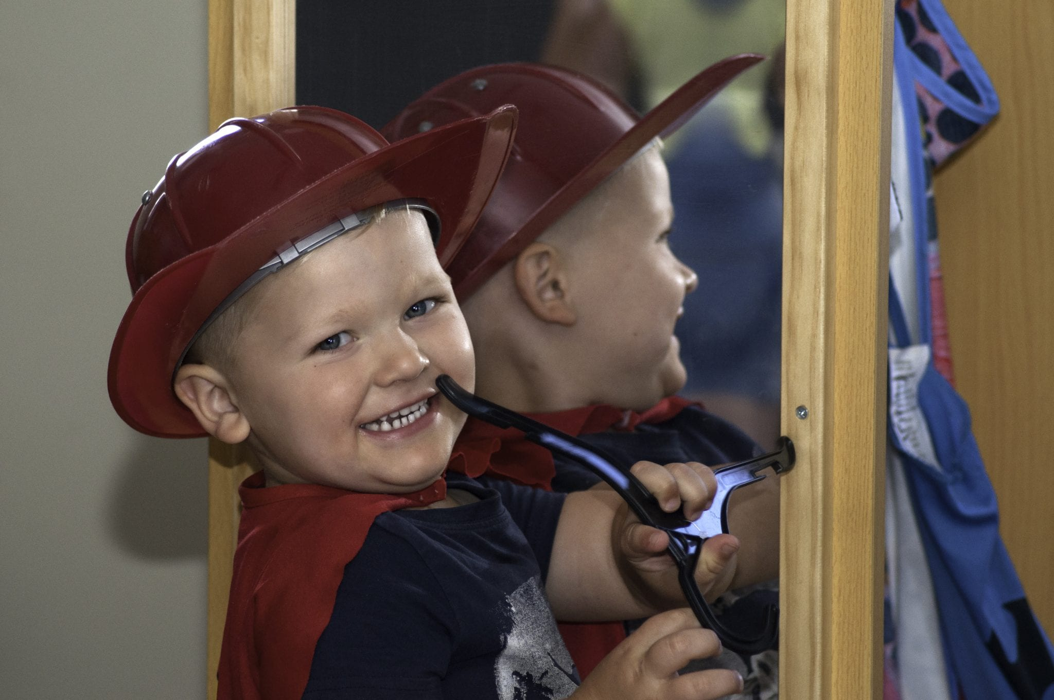 young-boy-with-red-fireman-hat-and-cape-smiling-mirror-in-background