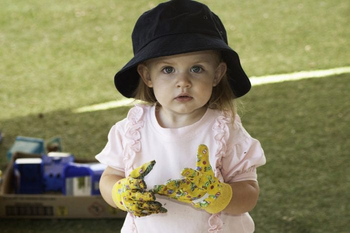 little girl with yellow gardening gloves and a sun hat