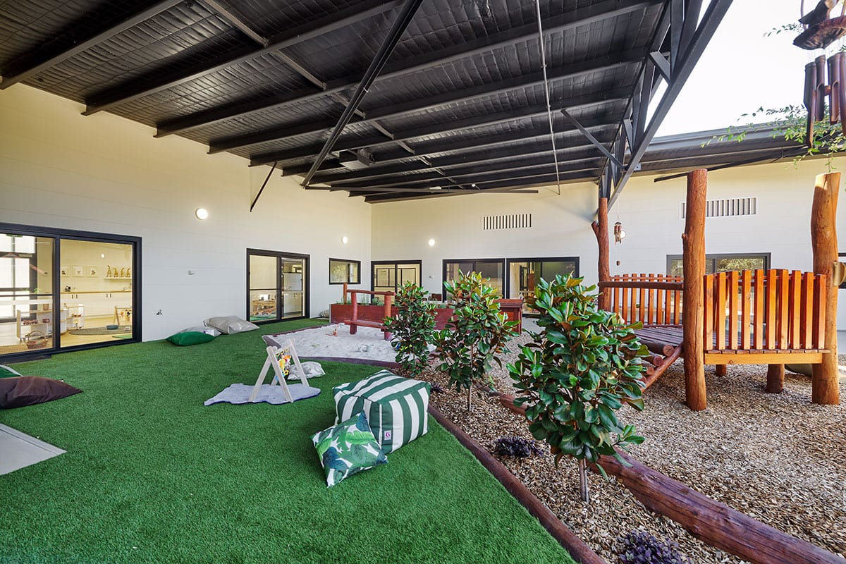 Babies outdoor area with green articial lawn and wooden sitting