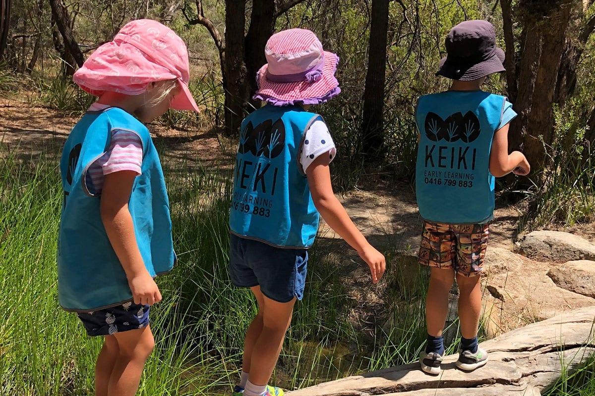 Vacation Care children walking on log in natural bushland