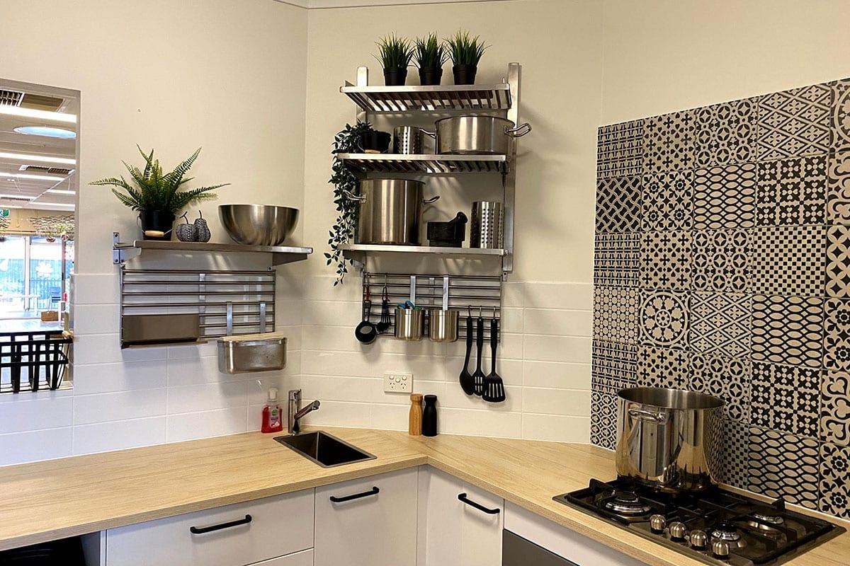 Modern kitchen interior of keiki mindarie keys with steel utensils kept on shelves