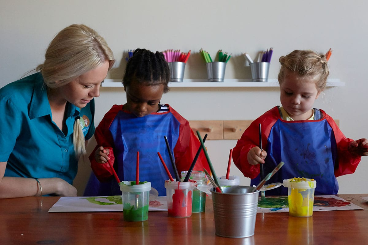 kindy aged children painting with educator