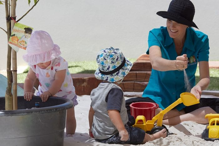 early childhood educator playing with two babies in sandpit