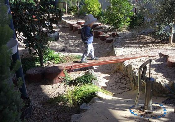 Child balancing on beam in Keiki Trinity childcare garden