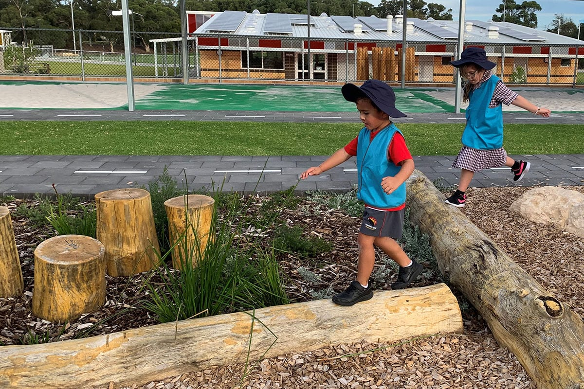 Boy and girl playing on school nature playground
